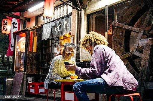 Couple sitting outside Japanese Izakaya using mobile phone, social media, online messaging