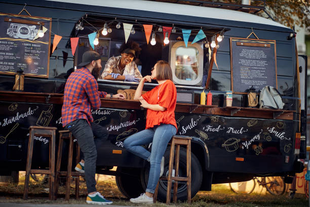 Hipster couple ordering from food truck; Urban lifestyle concept stock photo