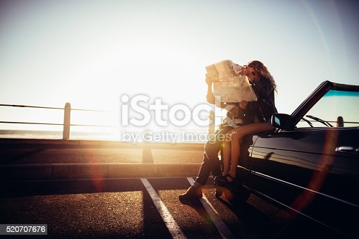 Happy hipster couple leaning against a vintage convertible on seaside looking at a map to plan a summer road trip