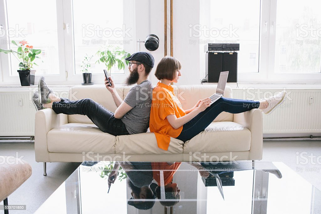 hipster couple sit on couch and look into digital devices stock photo