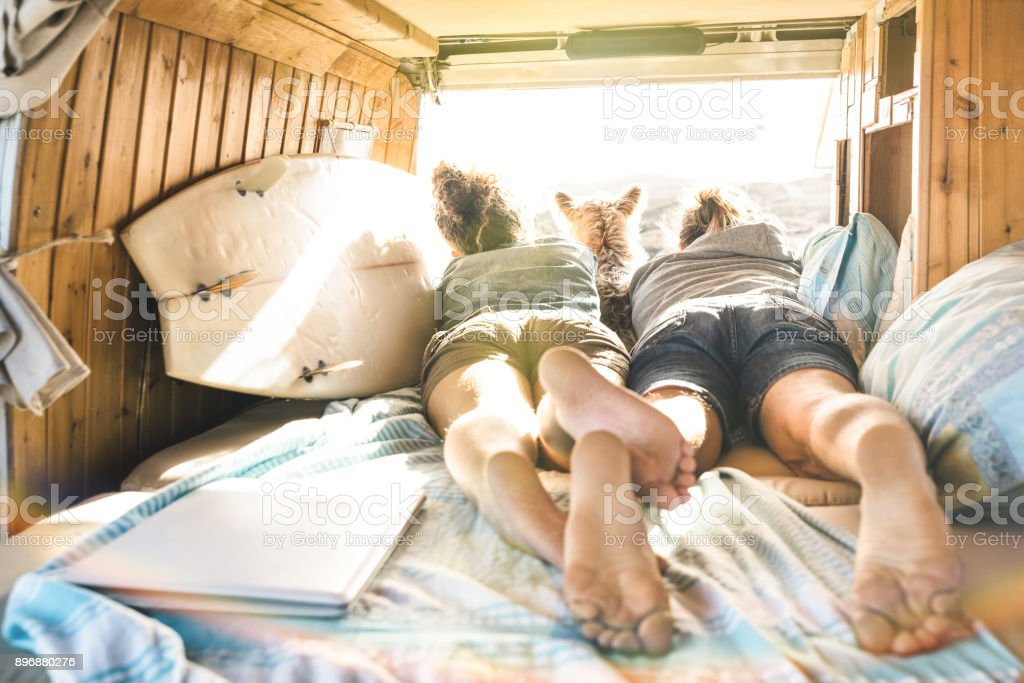 Hipster couple with cute dog traveling together on vintage van transport - Life inspiration concept with hippie people on minivan adventure trip watching sunset in relax moment - Warm sunshine filter stock photo