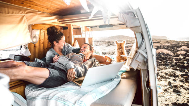 Hipster couple with dog traveling together on retro mini van transport - Digital nomad concept with indie people on minivan romantic trip working at laptop pc in relax moment - Warm contrast filter stock photo