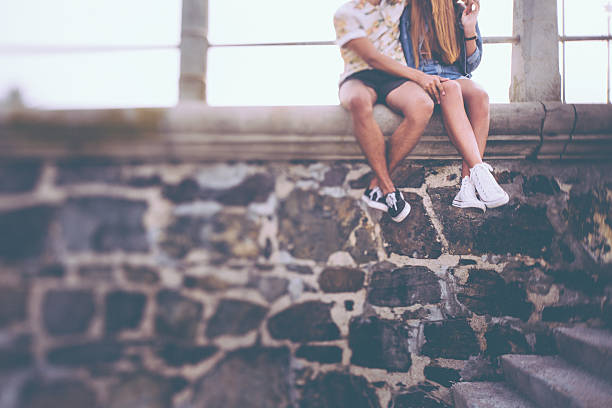 Hipster Paares Beinen sitzt auf eine Steinmauer – Foto