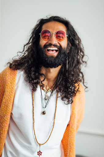 A portrait shot of a mid aged Pakistani man laughing and looking at the camera. He is wearing bohemian clothing and jewellery, sunglasses and has a large black beard and long curly hair.