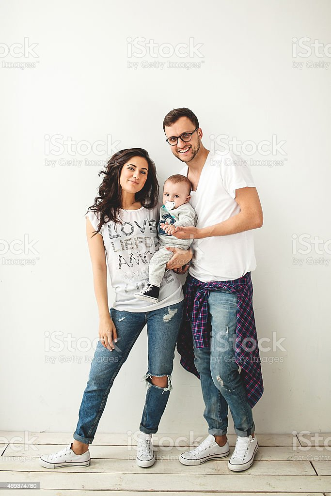 Hipster father, mother holding cute baby boy over white backgrou stock photo