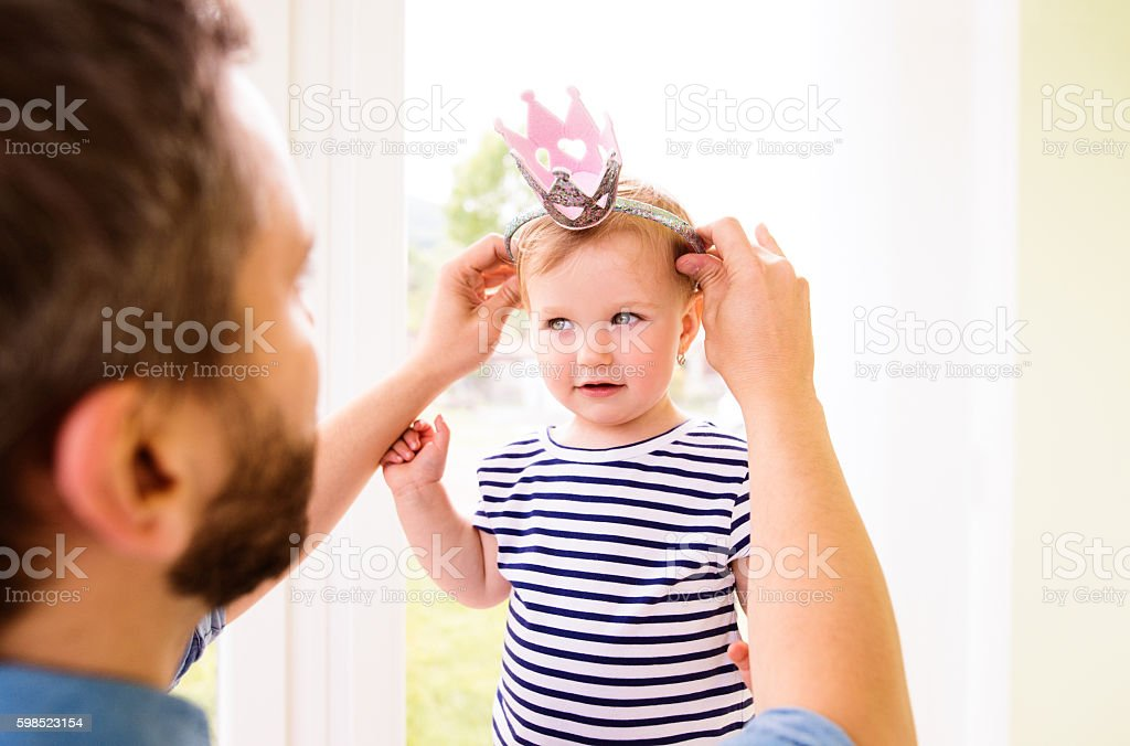Hipster father with daughter putting crown on her head stock photo