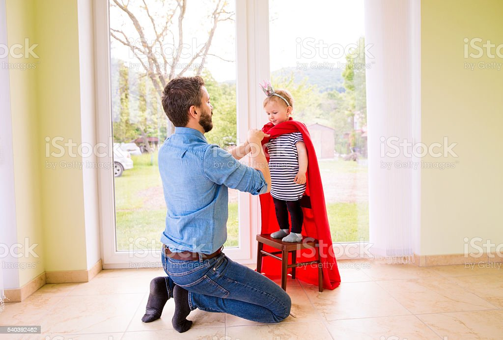 Hipster father with princess daughter in red superhero cape stock photo