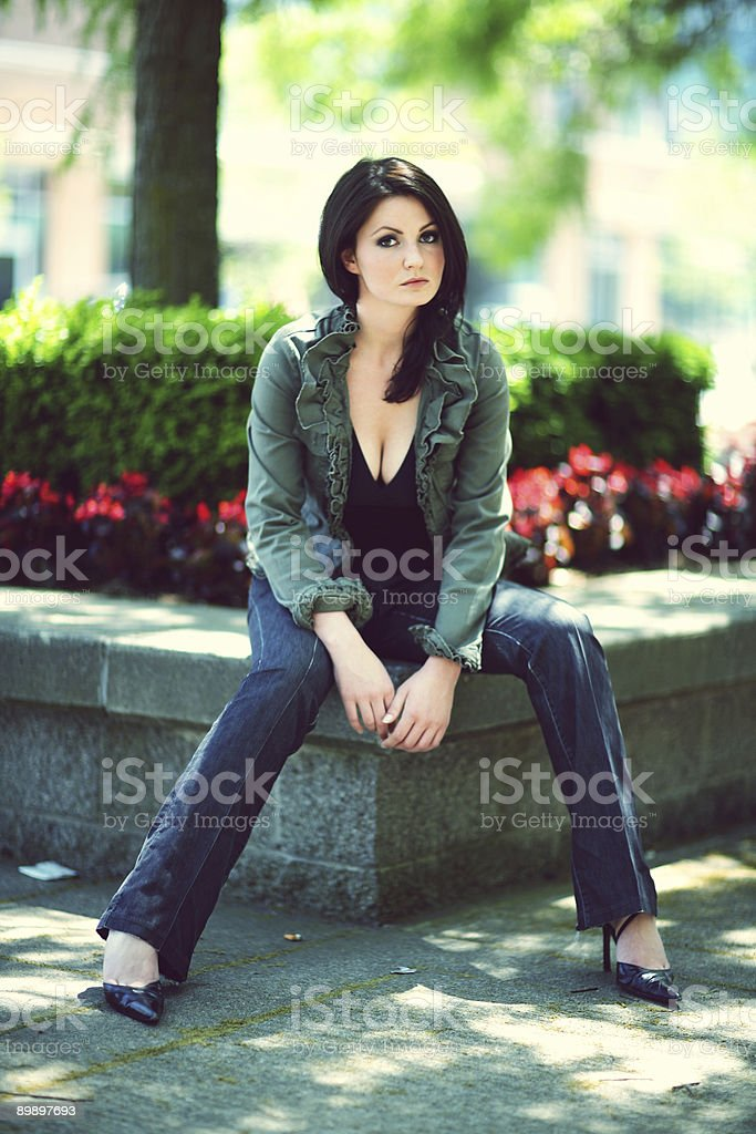 Hipster Female Sitting on Cement Flower Bed royalty-free stock photo