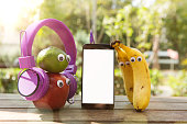 Hipster Fresh Fruits with headphones looking smartphone