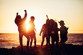 istock Hipster friends dancing in sunset light at a beach 514389408