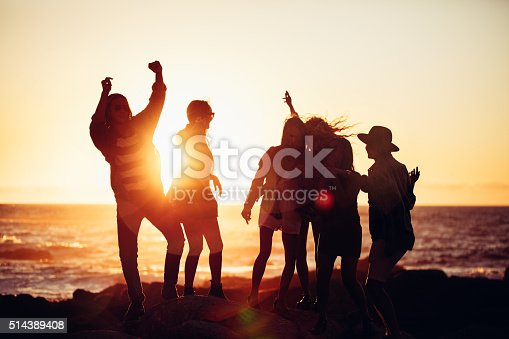 Group of fun loving hipser friends dancing with raised arms and partying at sunset on a beach in summertime