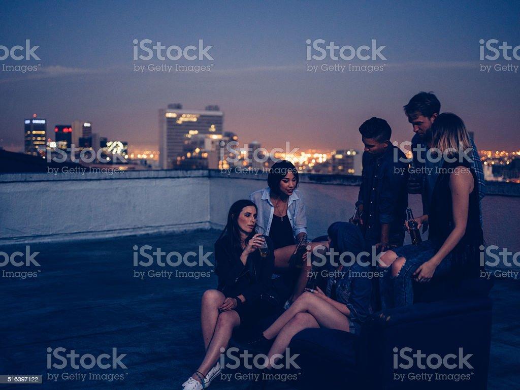 Hipster amis boire un verre et discuter sur une fête sur le toit - Photo