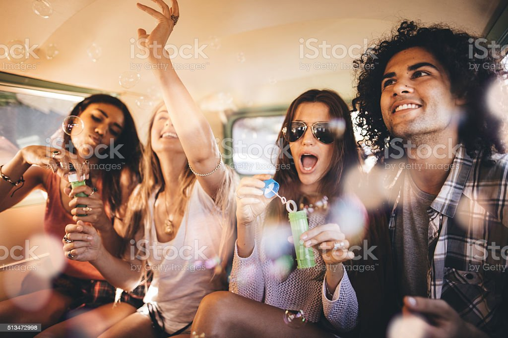 Hipster friends having bubbles party inside a vintage van stock photo