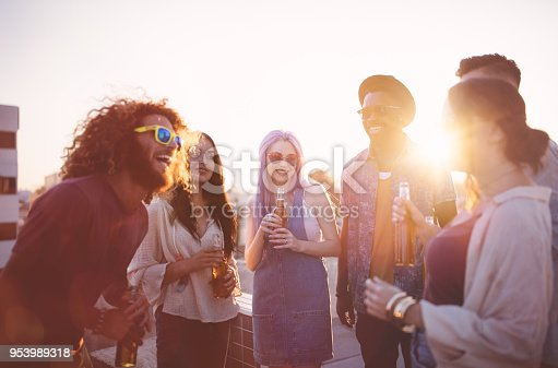 istock Hipster friends having fun and drinking beer at rooftop party 953989318