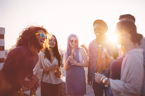 Multi-ethnic group of young friends enjoying their drinks and laughing at summer rooftop party