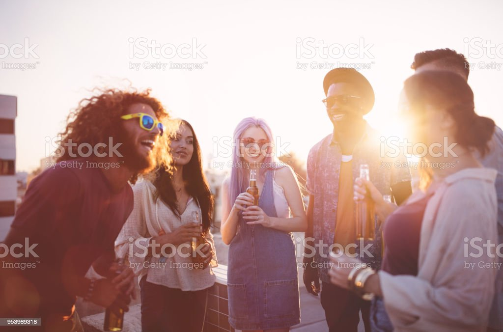 Hipster friends having fun and drinking beer at rooftop party stock photo