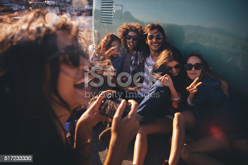 Group of friends dressed in hipster style posing for pictures showing peace sign and toothy smiles sitting close to their vitage van during a road trip