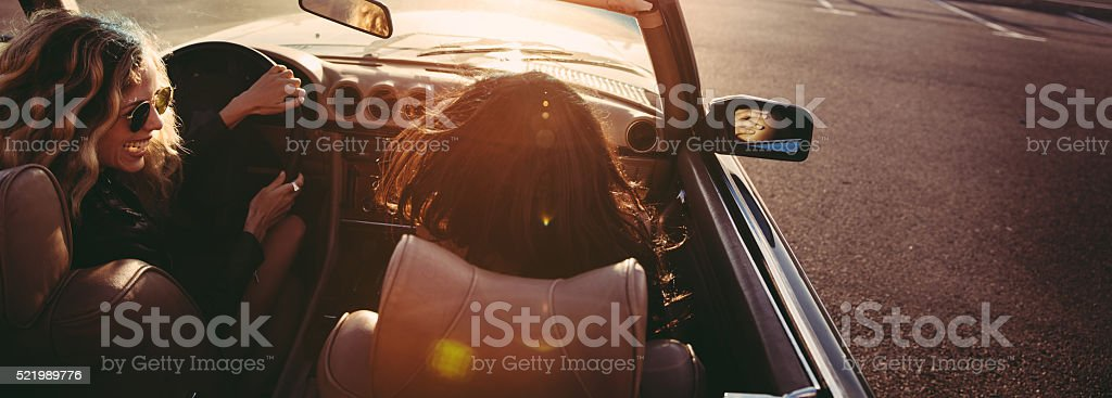 Hipster friends sitting in a vintage convertible enjoying the su stock photo