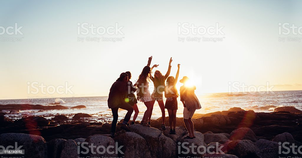 Hipster fun loving friends dancing at beach on sunset stock photo