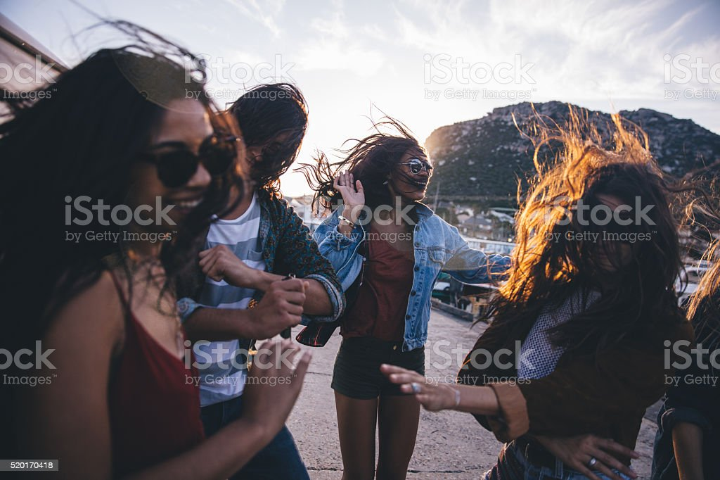 Hipster fun loving friends dancing at the harbor on sunset stock photo