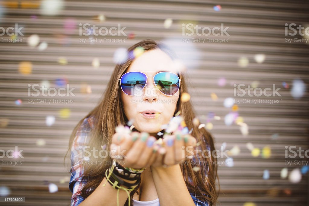 Hipster girl blowing confetti from hands stock photo