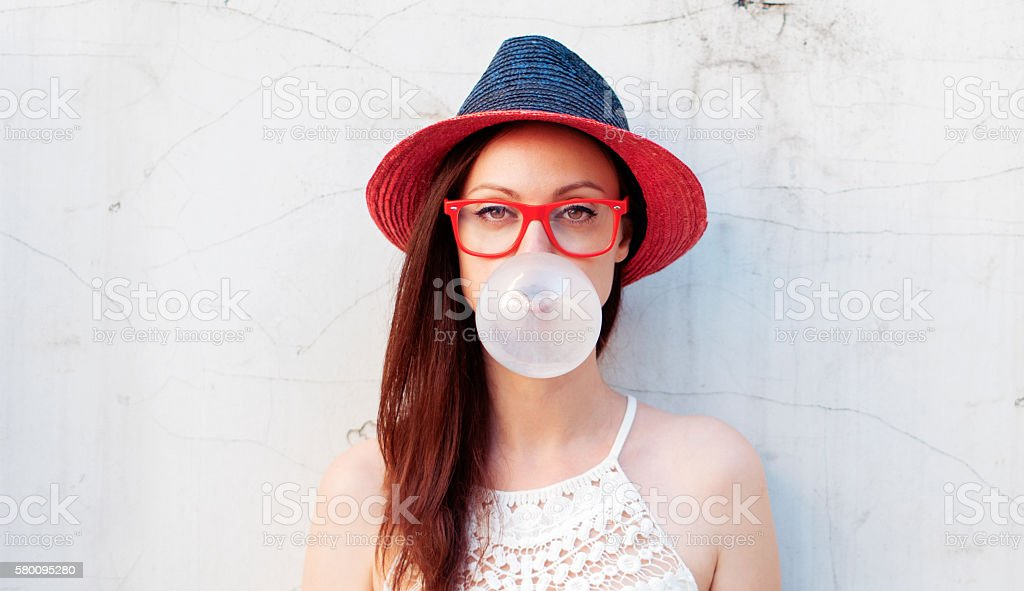Hipster girl blows big bubble from bubble gum stock photo