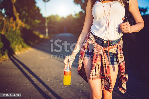 Cute hipster girl carrying juice in a park.