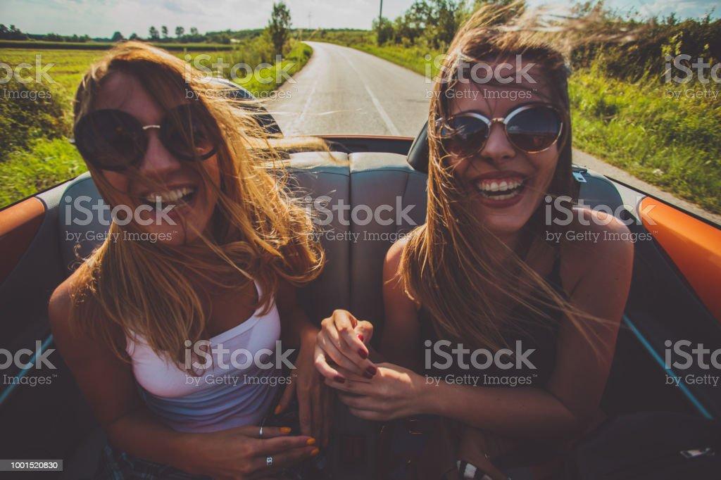 Hipster girl friends enjoys a summer road trip