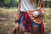 Hipster girl holding a baseball ball in a baseball glove outdoors