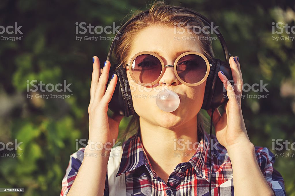Hipster girl listening to music on headphones and chews cud. stock photo