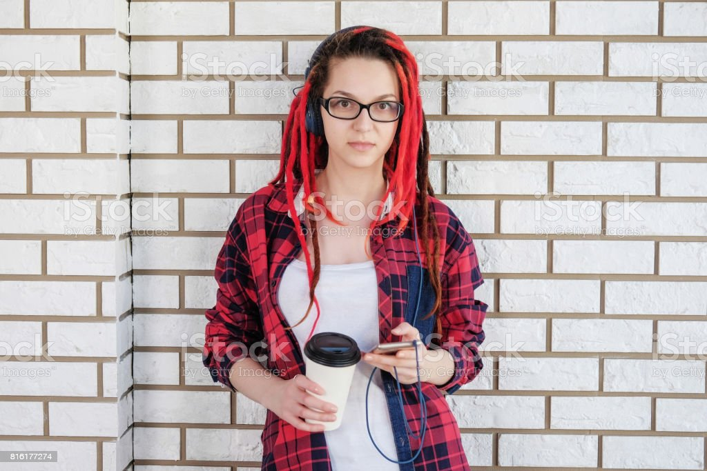 Hipster girl listening to music with headphones, drinking coffee to go and rewrite in social networks on the smart phone. stock photo
