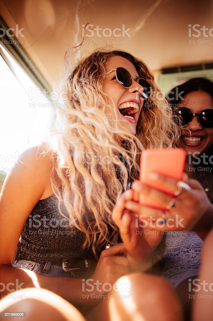 Hipster girl looking at smart phone with road trip friend stock photo