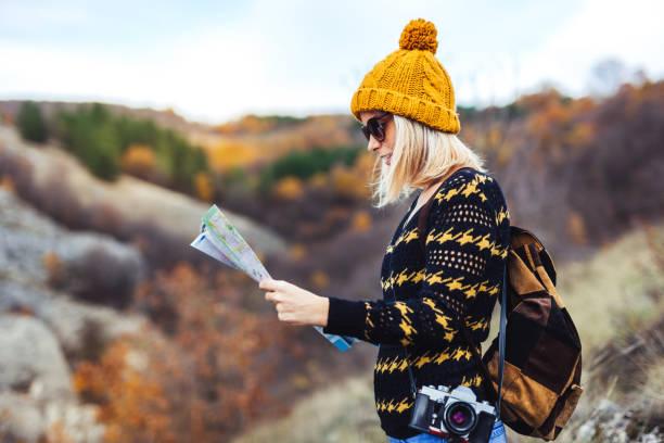 hipster mädchen auf der karte auf dem berg suche - geführtes lesen stock-fotos und bilder