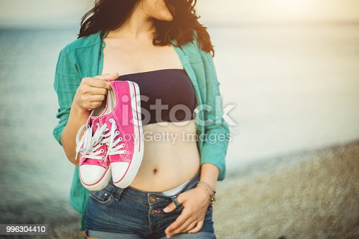 Young Caucasian hipster girl is standing on a sea beach at sunset time, wearing denim shorts, top and unbuttoned light green shirt, holding pair of pink sneakers in her hand.