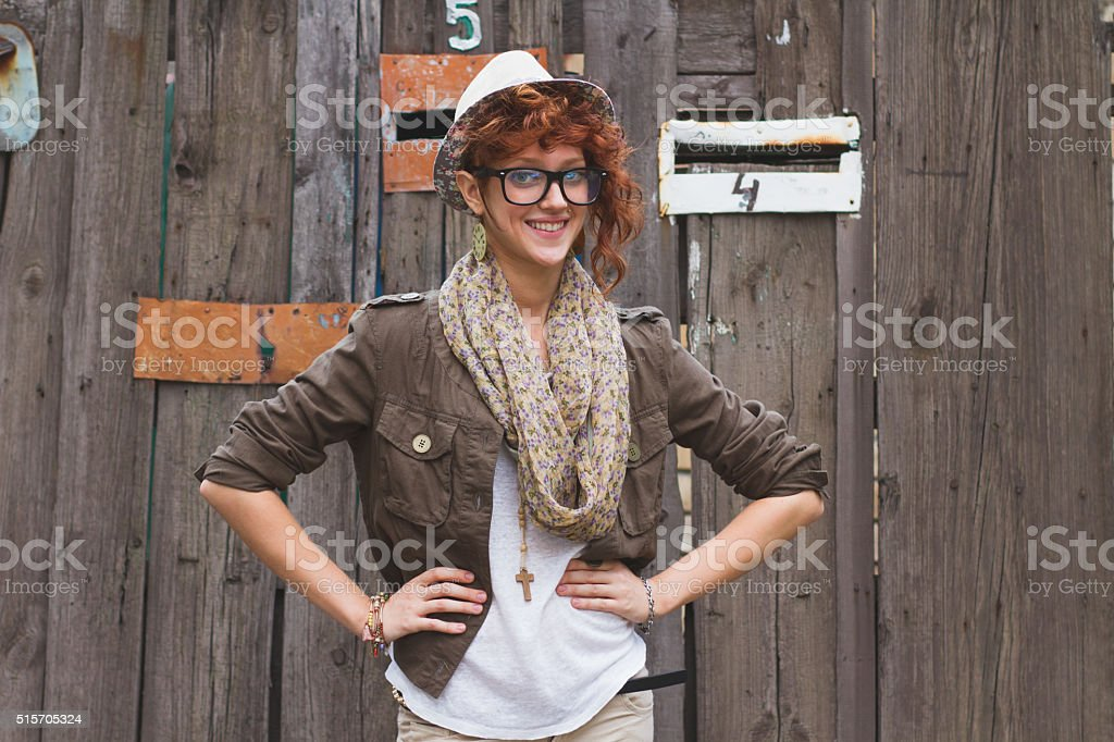 Hipster girl posing at wooden background stock photo