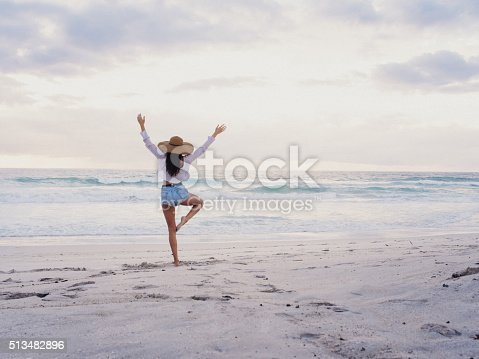 Brunette hipster girl in shorts and hat, practices yoga tree pose while facing the ocean on a sandy beach