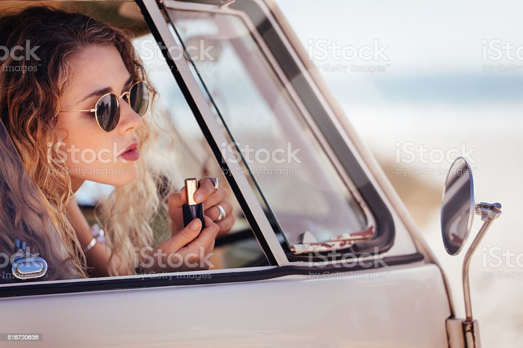 Hipster Girl Putting on Lipstick in Sideview Mirror of van stock photo