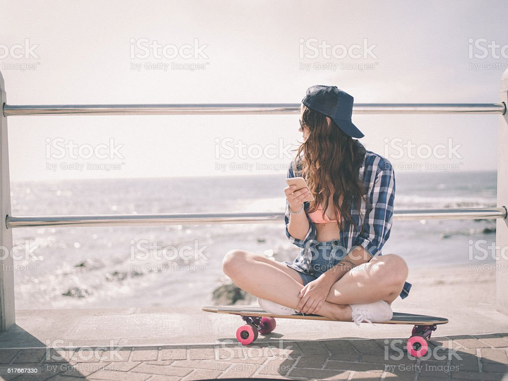 Hipster girl sitting on her skateboard at the beachfront stock photo