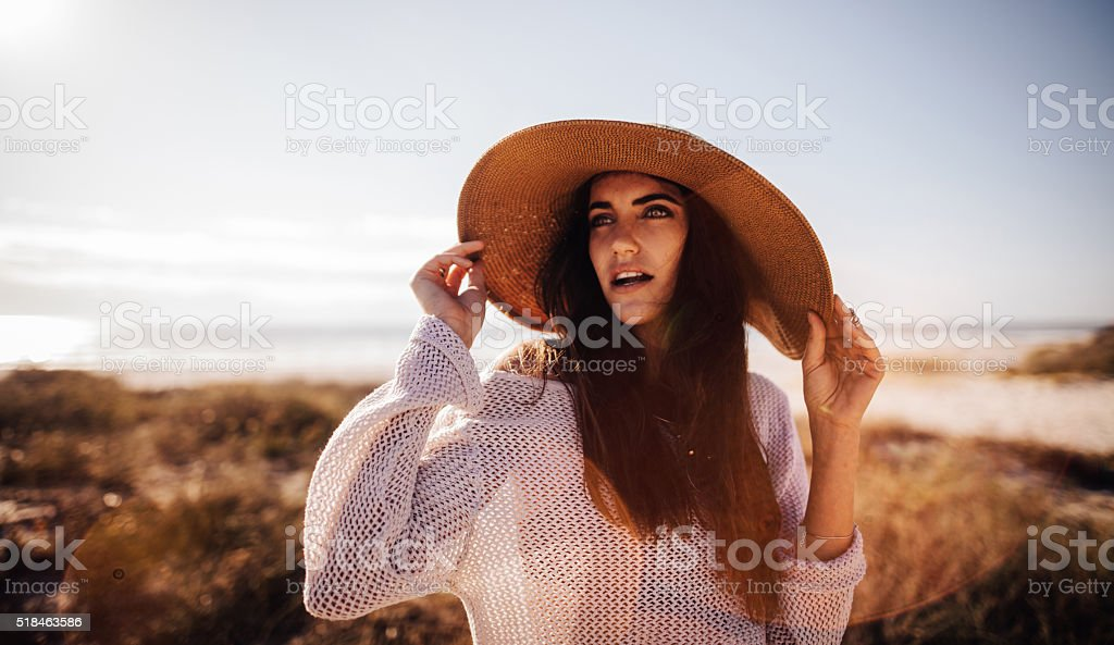Hipster Girl  Smiling and Posing with Hat on Sandy Beach stock photo