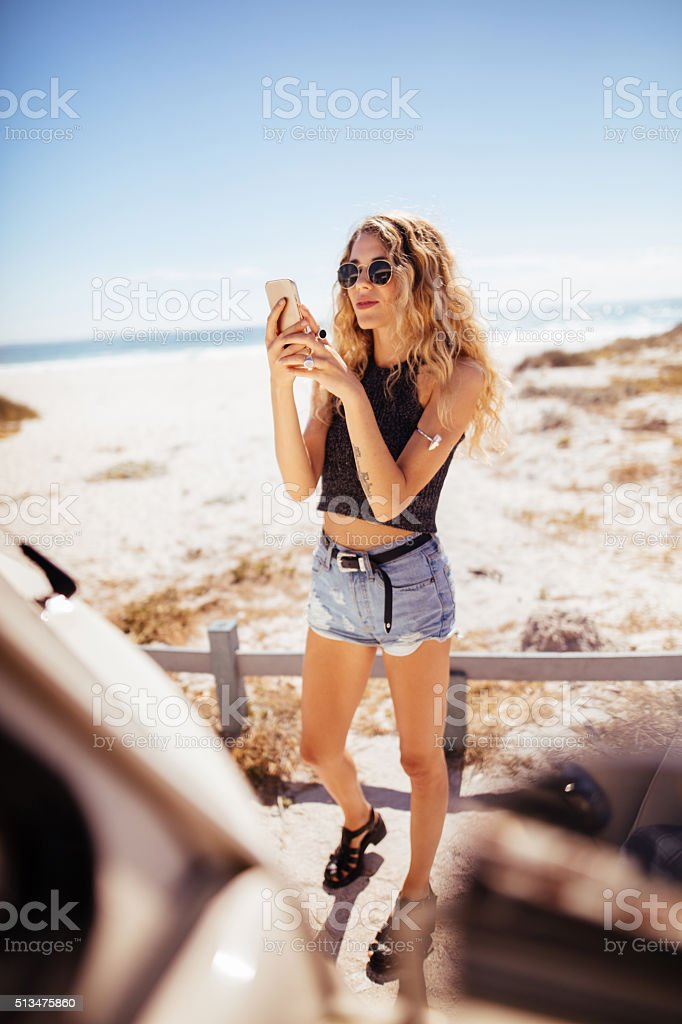 Hipster Girl taking Photo of road trip van with Phone stock photo