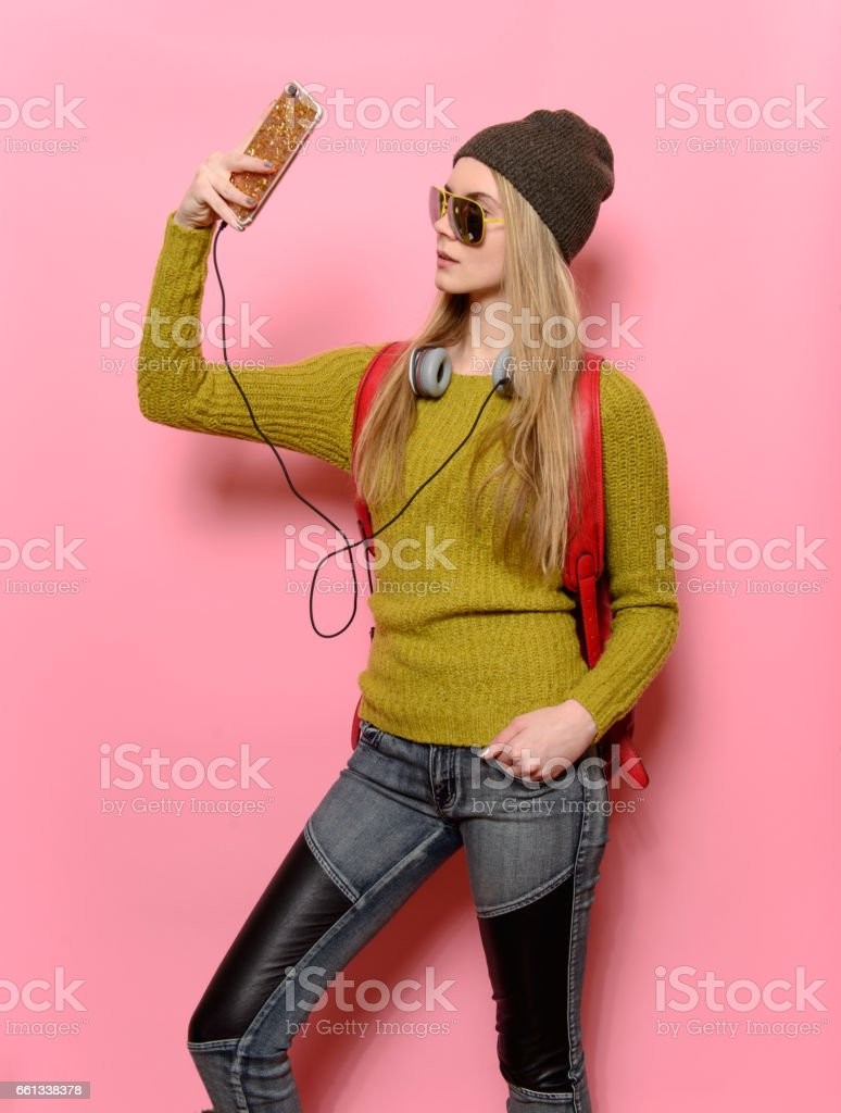 Hipster girl taking selfie on mobile phone and listen music stock photo
