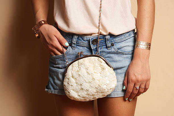 hipster girl wearing cute trendy outfit jeans shorts with bag - armband vintage stock-fotos und bilder