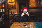 Hipster girl with a red knit hat enjoying the coffee at a coffee shop
