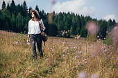 Hipster girl with backpack traveling in sunny mountains, walking in  wildflower meadow. Stylish happy woman in hat exploring and hiking on top of mountain. Wanderlust and travel concept