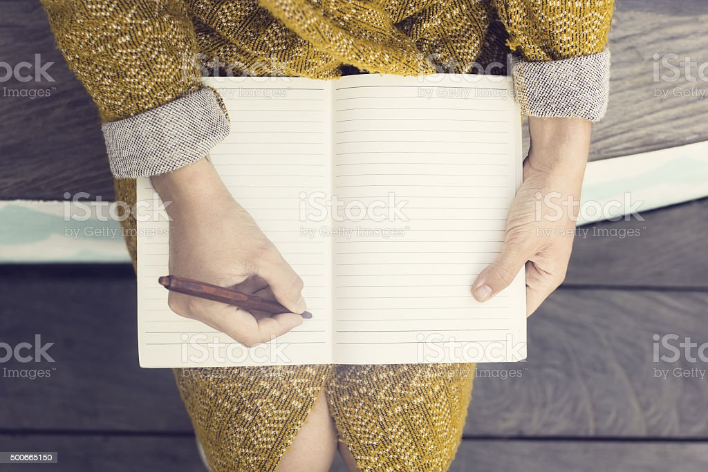 Hipster girl with blank diary and pen sitting stock photo