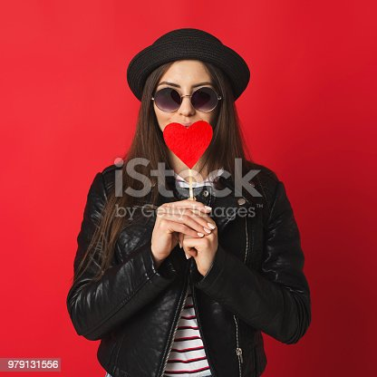 529664088istockphoto Hipster girl with red heart wearing leather jacket at studio background 979131556