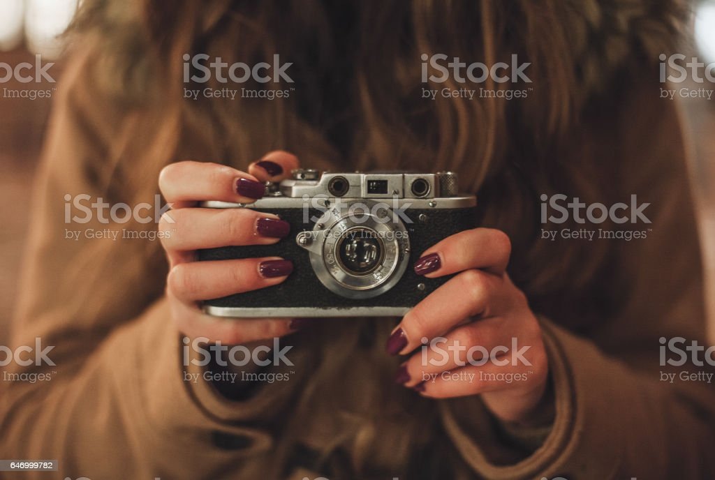 Hipster girl with retro camera taking photos outdoors - Photo