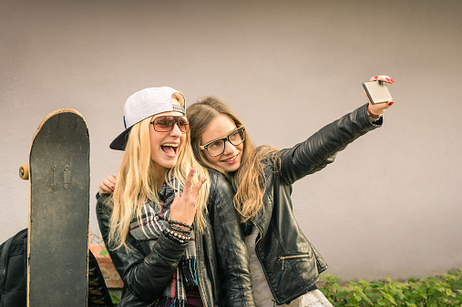 Hipster girlfriends taking a selfie in urban city context