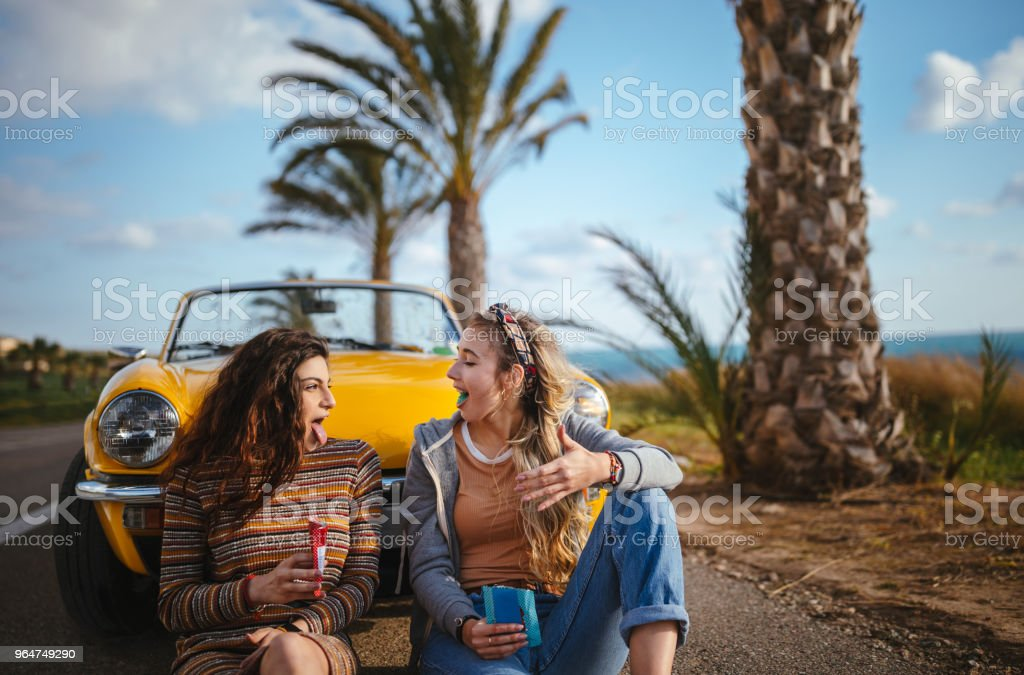 Hipster girls eating candy on road trip with convertible car royalty-free stock photo