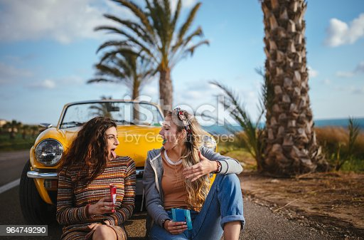 147878016 istock photo Hipster girls eating candy on road trip with convertible car 964749290